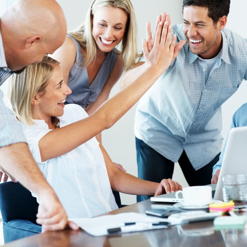 Portrait of an excited businesspeople giving each other high five for successful business at office